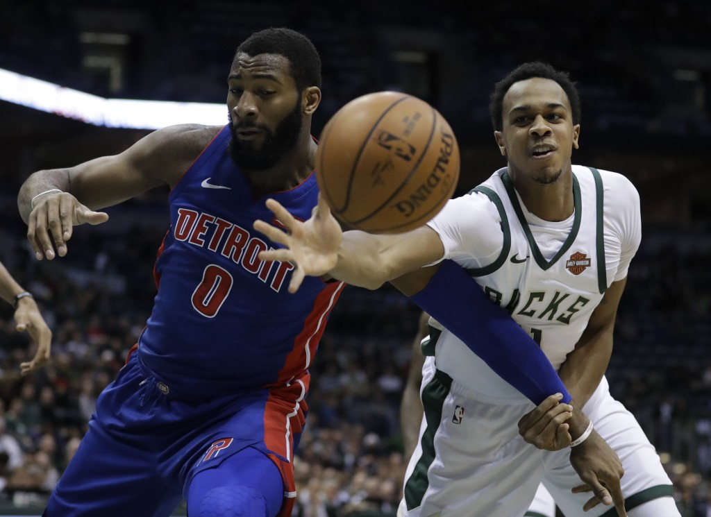 Detroit Pistons' Andre Drummond and Milwaukee Bucks' John Henson go after a loose ball during the first half of an NBA basketball game Wednesday, Dec.