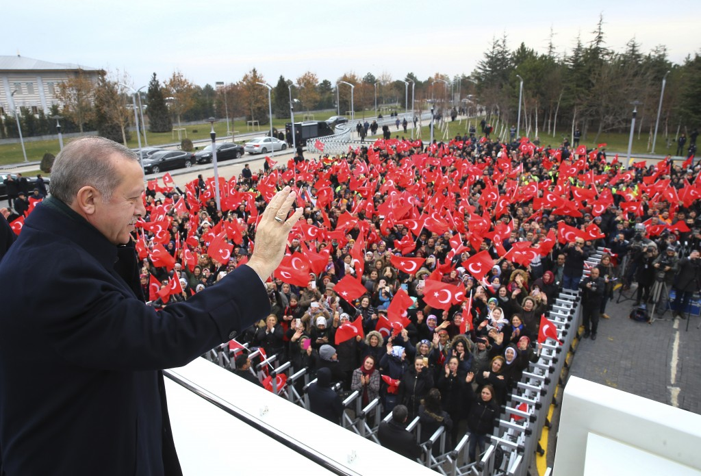Turkey's President Recep Tayyip Erdogan waves to a group of workers at the airport in Ankara, Turkey, Thursday, Dec. 7, 2017 prior to his departure on