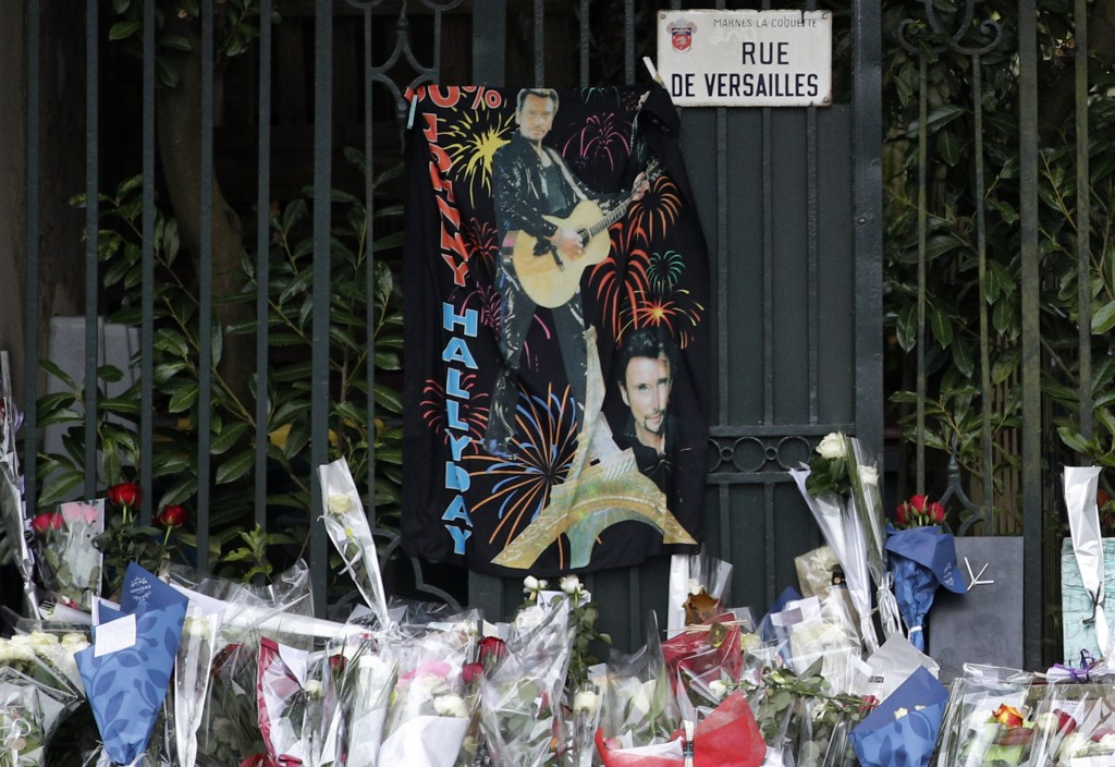 Flowers brought by fans lay outside Johnny Hallyday's house in Marnes-la-Coquette, outside Paris, Thursday, Dec.7, 2017. Johnny Hallyday, France's big