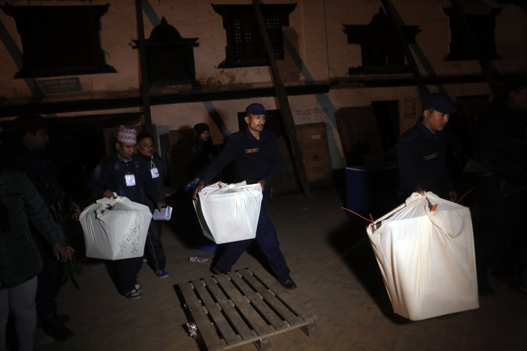 Nepalese policemen and election commission staff carry ballot boxes after the completion of polling in Kathmandu, Nepal, Thursday, Dec. 7, 2017. Milli