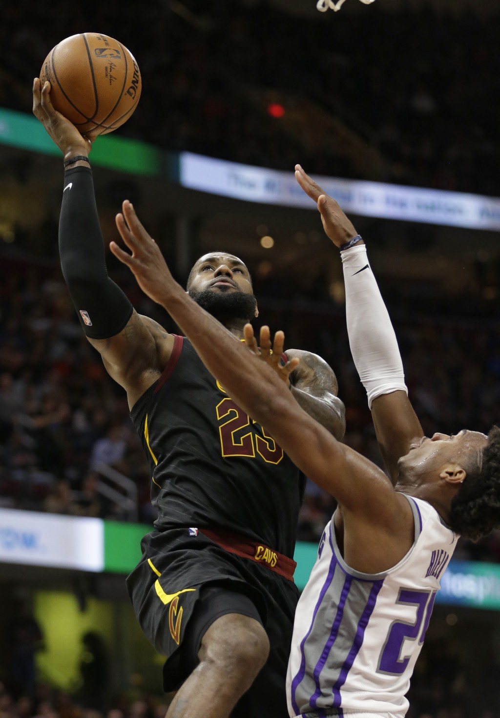 Cleveland Cavaliers' LeBron James (23) drives to the basket against Sacramento Kings' Buddy Hield (24), from the Bahamas, in the first half of an NBA