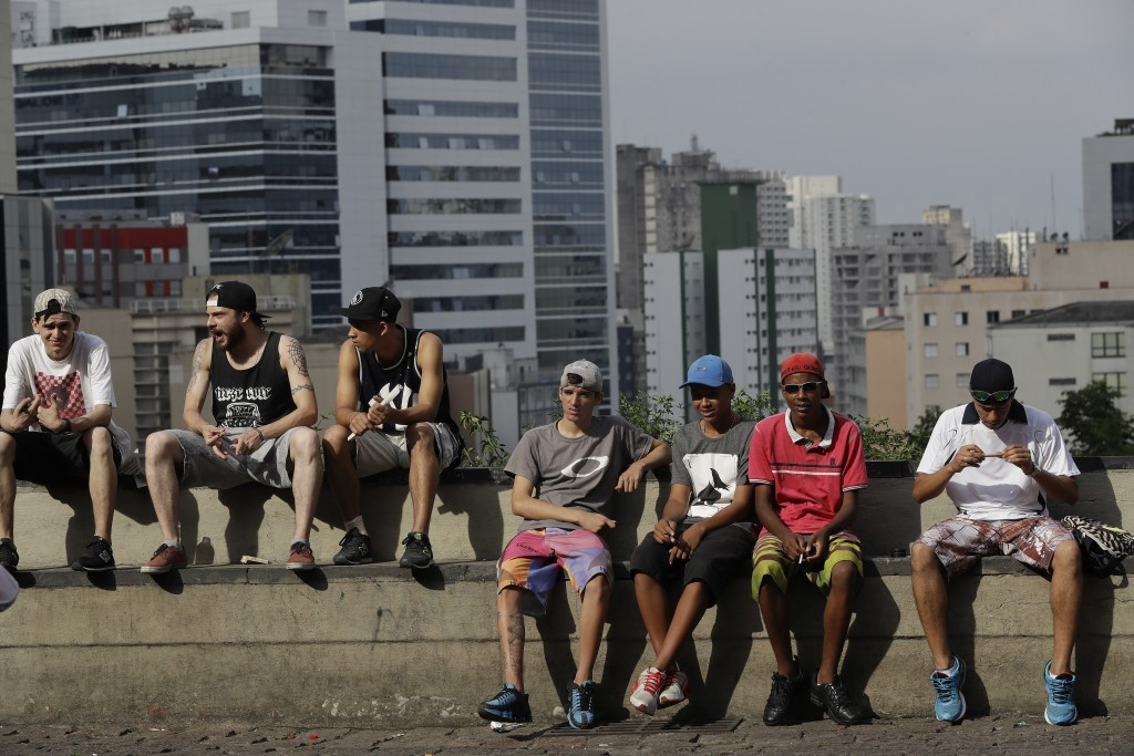 In this Dec. 5, 2017 photo, youth sit on a wall outside the art museum, in Sao Paulo, Brazil. The country's byzantine political party system and rampa