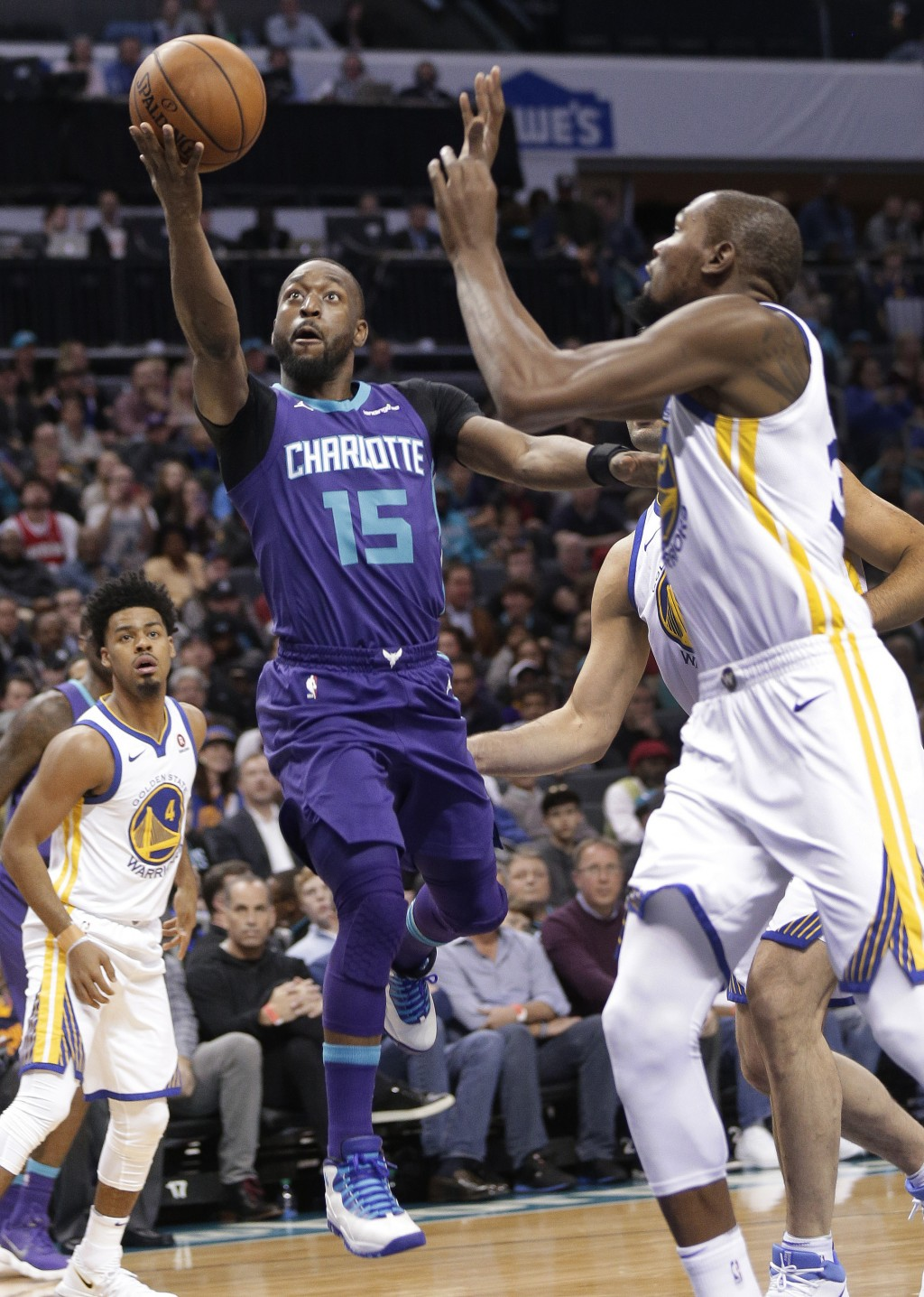 Charlotte Hornets' Kemba Walker (15) drives past Golden State Warriors' Kevin Durant (35) during the first half of an NBA basketball game in Charlotte