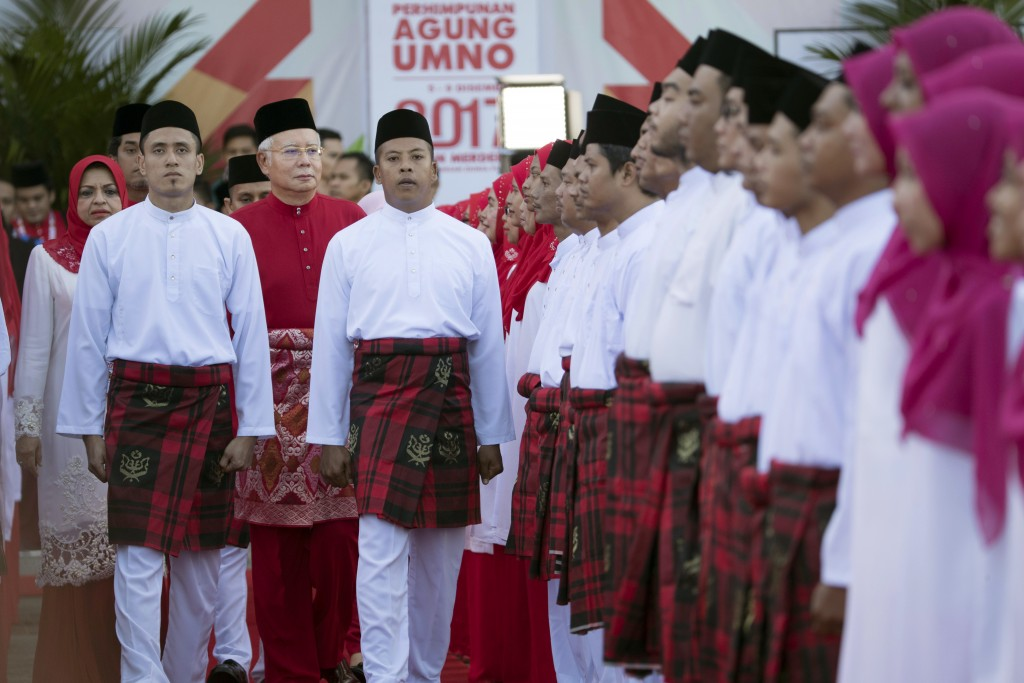 United Malays National Organisation (UMNO) party President and Malaysian Prime Minister Najib Razak, wearing red shirt at center left, inspects a cere