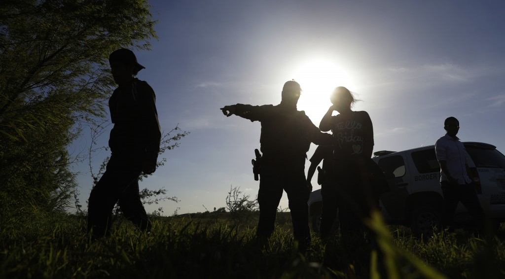 In this Aug. 11, 2017, photo U.S. Customs and Border Patrol agents pick up immigrants suspected of crossing into the United States illegally along the