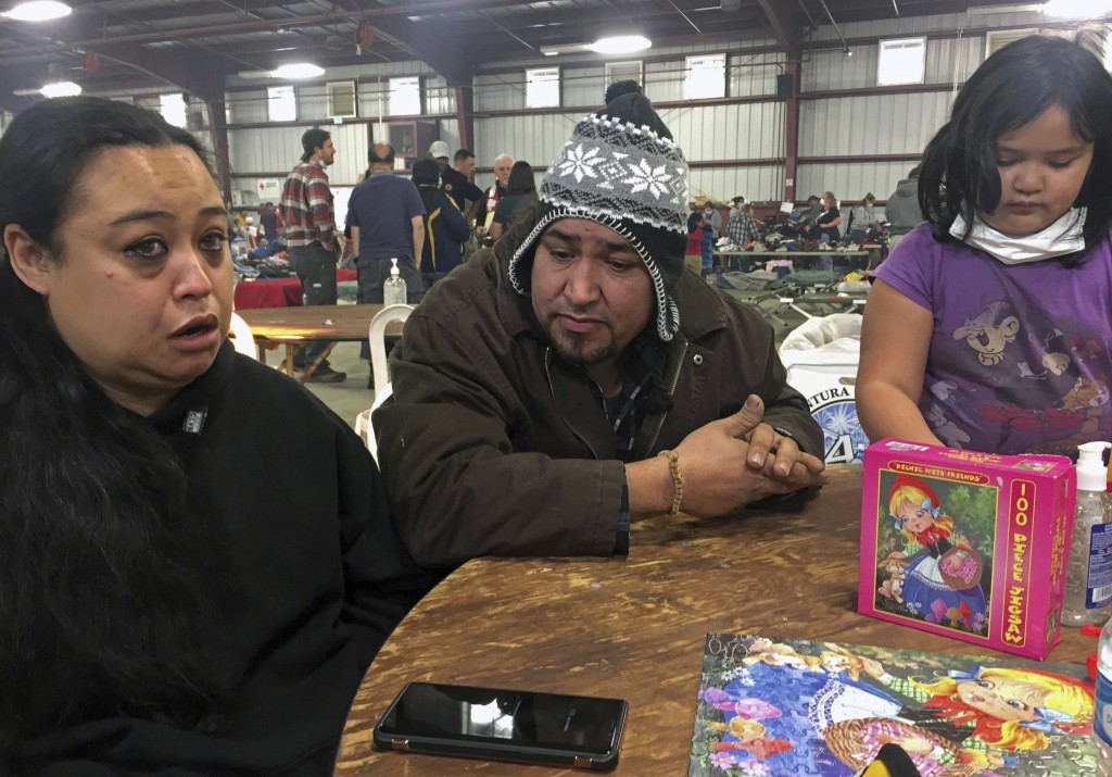 Wildfire survivors Marolyn Romero-Sim left, and Hugo Romero-Rodriguez, middle, and their 9-year-old daughter, Milagros, sit inside the evacuation cent