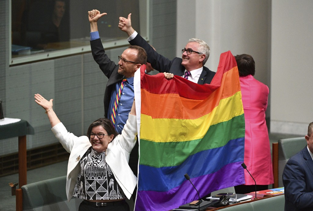 Members of parliament, from left, Cathy McGowan, Adam Brandt and Andrew Wilkie celebrate the passing of the Marriage Amendment Bill in the House of Re