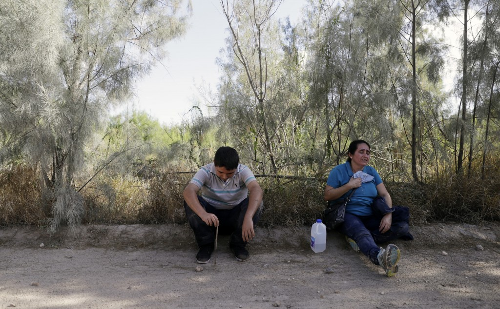 In this Aug. 11, 2017, photo, over heated immigrants suspected of crossing into the United States illegally along the Rio Grande near Granjeno, Texas,