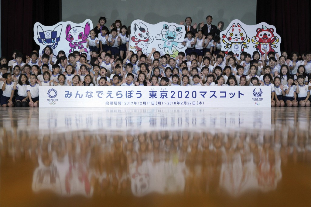 Children and officials of Tokyo 2020 pose for photographers with cutouts of shortlisted three mascot design sets which each contain one mascot for the