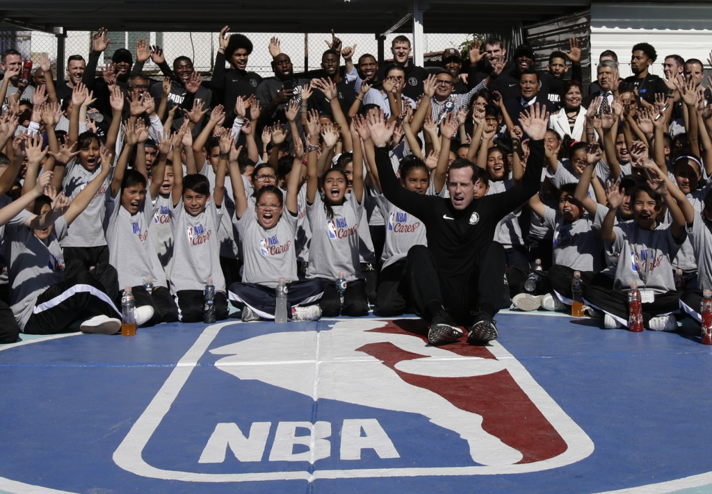 Brooklyn Nets players and coaches, including head coach Kenny Atkinson, front, pose for a picture with children after teaching them basketball skills