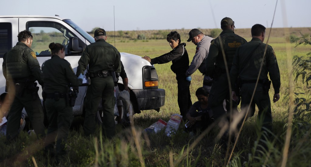 In this Aug. 11, 2017, photo, immigrants suspected of crossing into the United States illegally along the Rio Grande near Granjeno, Texas, are held by
