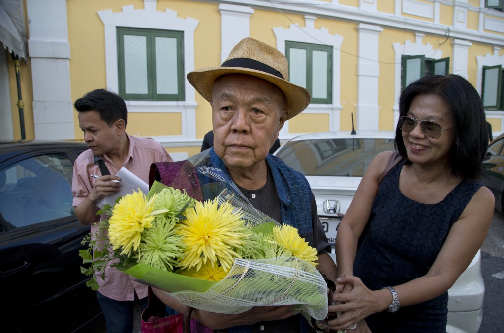 Sulak Sivaraksa, center receives flowers from a well-wisher outside a military court Thursday, Dec. 7, 2017 in Bangkok, Thailand as he walks in to fin