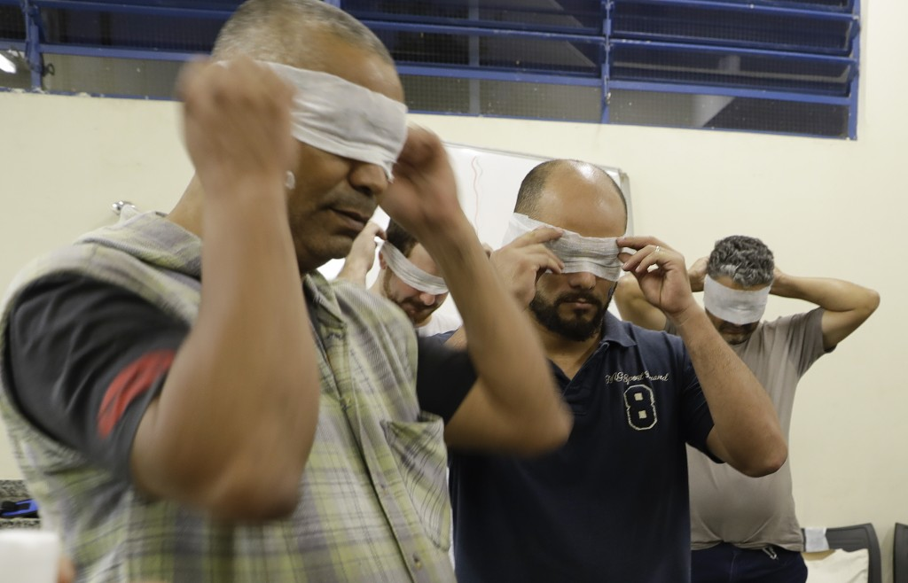 In this Nov. 28, 2017 photo, residents of the low-income Capao Redondo neighborhood and members of the Acredito movement are blindfolded as part of a