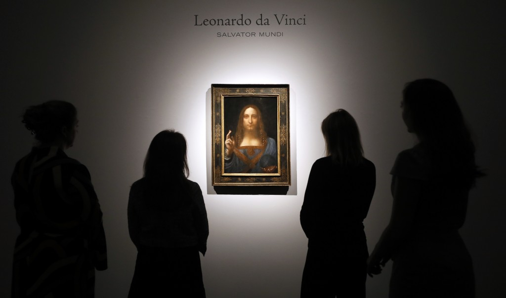 """FILE- In this Oct. 24, 2017, file photo, people gather around Leonardo da Vinci's """"Salvator Mundi"""" on display at Christie's auction rooms in London. T"""