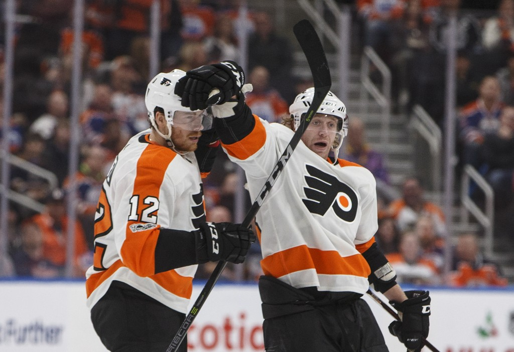 Philadelphia Flyers' Michael Raffl (12) and Jakub Voracek (93) celebrate a goal against the Edmonton Oilers during the third period of an NHL hockey g