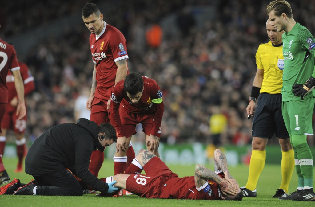 Liverpool's Alberto Moreno, center, receives a medical help during the Champions League Group E soccer match between Liverpool and Spartak Moscow at A