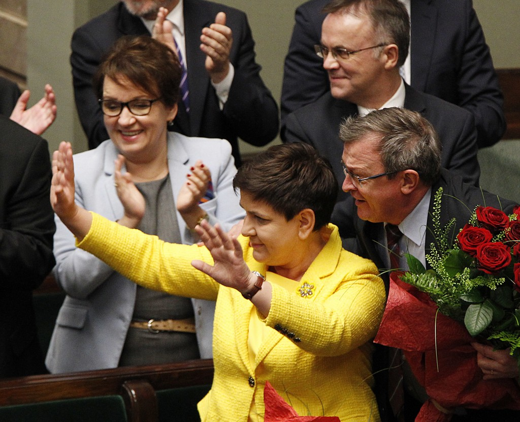 Poland's Prime Minister Beata Szydlo, left, rejoices after she and her government survived opposition's vote of no-confidence in the parliament in War