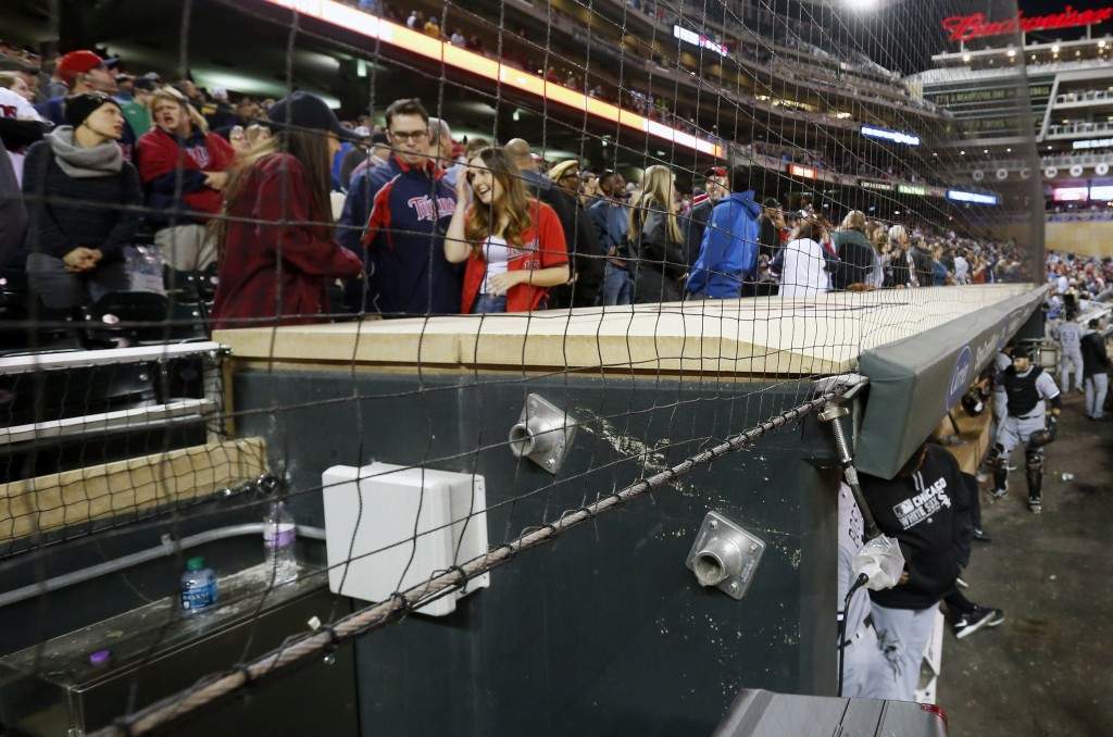 In this Wednesday, April 13, 2016 file photo, Minnesota Twins front row fans have protective netting to look through over the dugouts as they watch ba