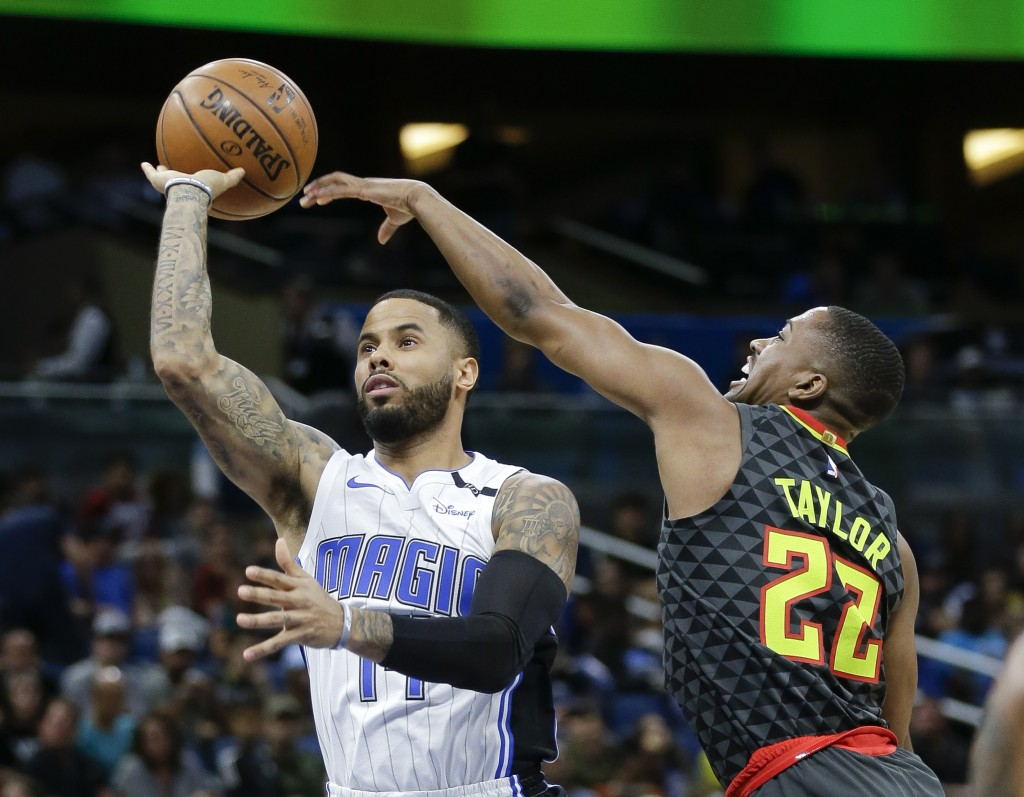 Atlanta Hawks guard Isaiah Taylor (22) deflects a shot attempt by Orlando Magic's D.J. Augustin, left, during the first half of an NBA basketball game