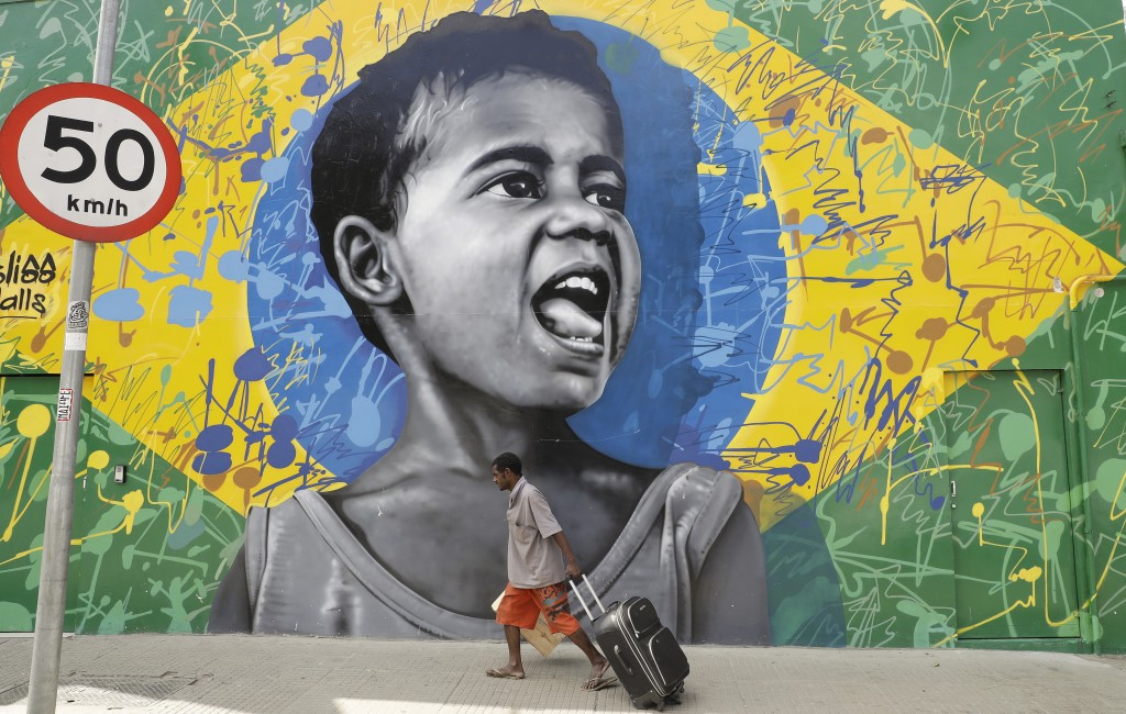 In this Dec. 5, 2017 photo, a man walks past a wall mural depicting a child superimposed on a representation of the Brazilian national flag, in Sao Pa