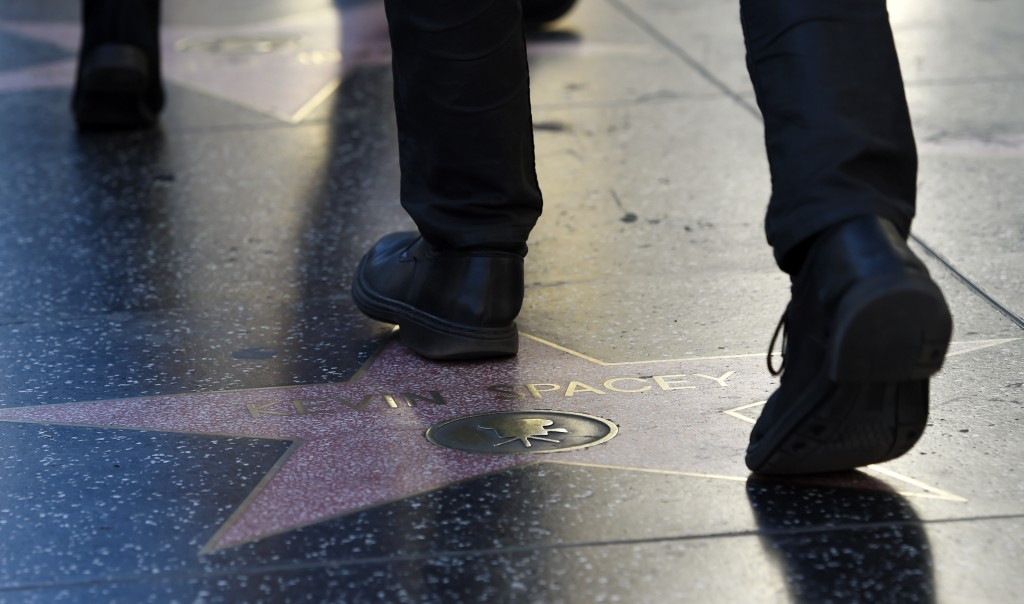 This Nov. 22, 2017 photo shows a pedestrian walking over the star of actor Kevin Spacey on the Hollywood Walk of Fame in Los Angeles. The ongoing sexu