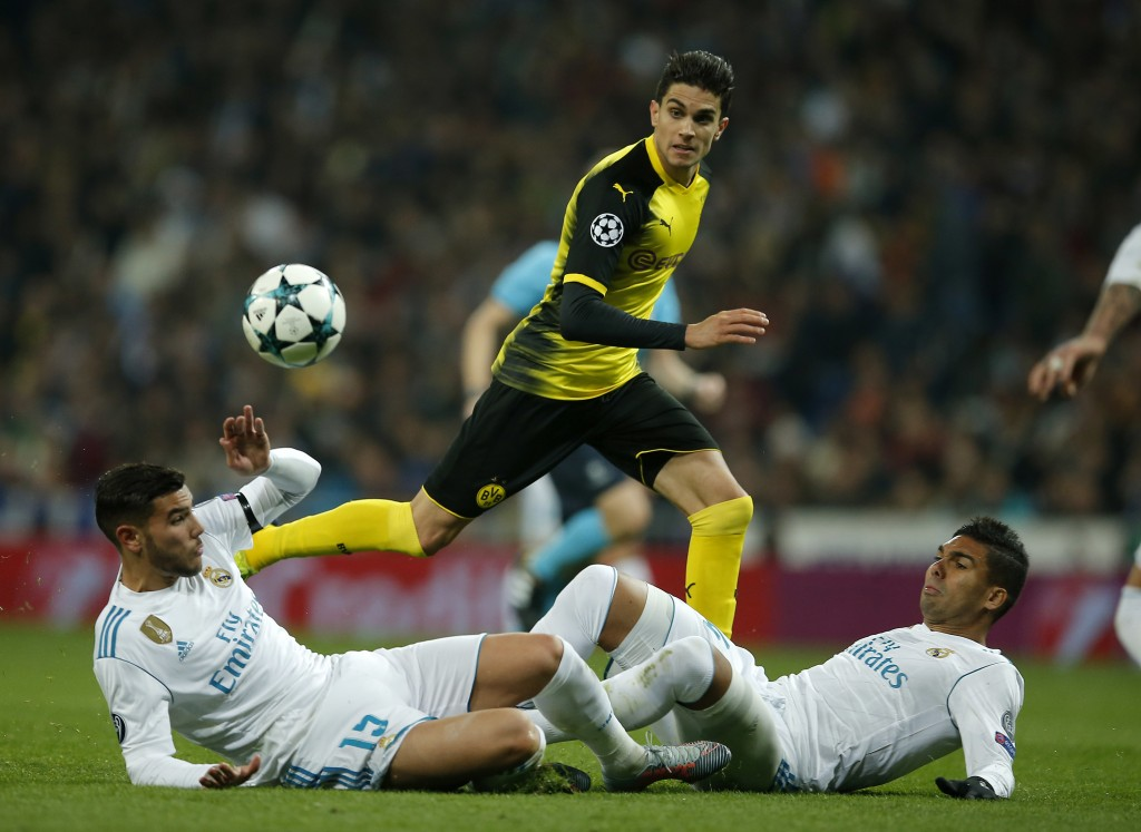 Dortmund's Marc Bartra, center, plays the ball over Real Madrid's Theo Hernandez, left, during the Champions League Group H soccer match between Real