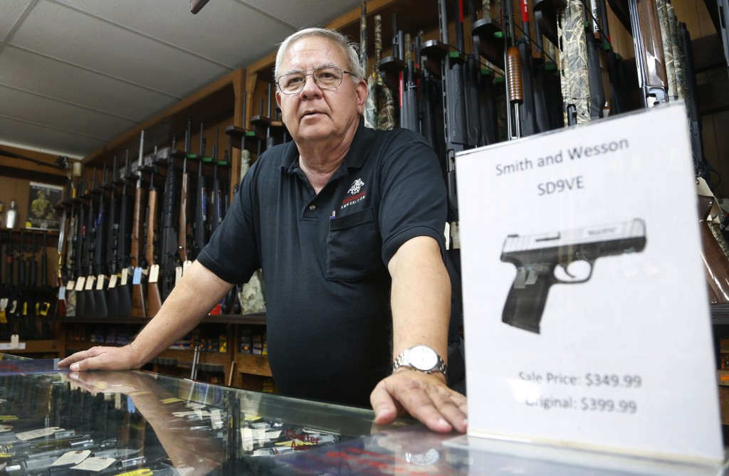 In this Tuesday, Dec. 5, 2017 photo, manager of Bob Moates Sports Shop, David Hancock, poses with a firearm in the shop in Richmond, Va. Hancock says