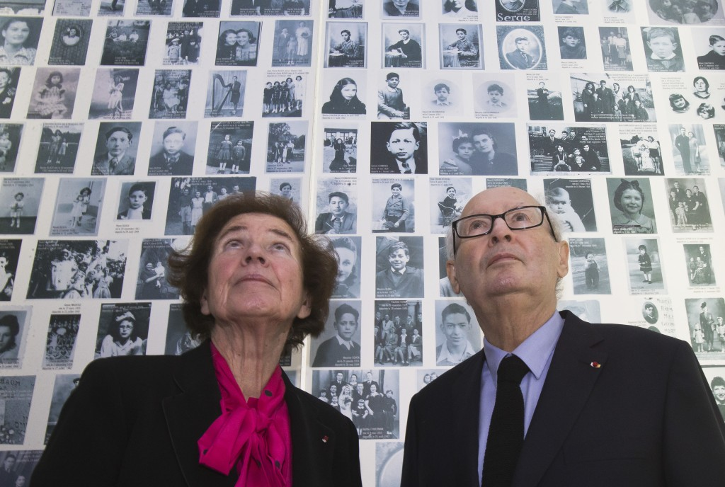 In this Tuesday, Dec. 5, 2017 photo, French Nazi hunters Beate Klarsfeld and her husband Serge Klarsfeld look at at photos of young Jews deported from