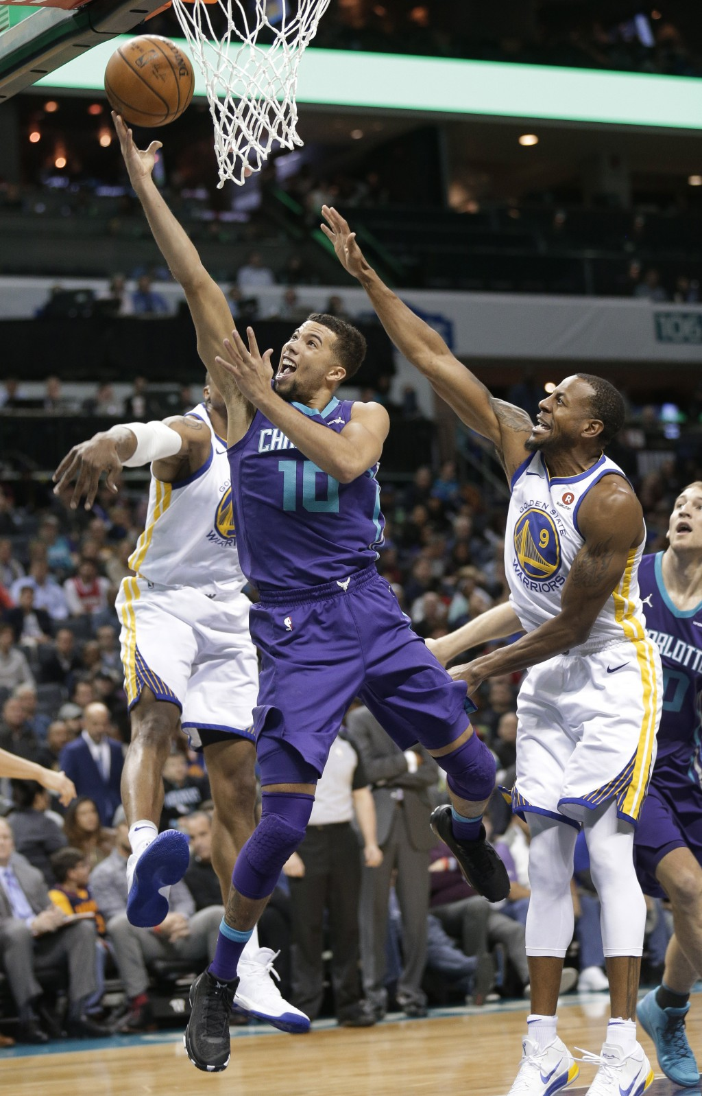 Charlotte Hornets' Michael Carter-Williams (10) drives past Golden State Warriors' Andre Iguodala (9) during the first half of an NBA basketball game