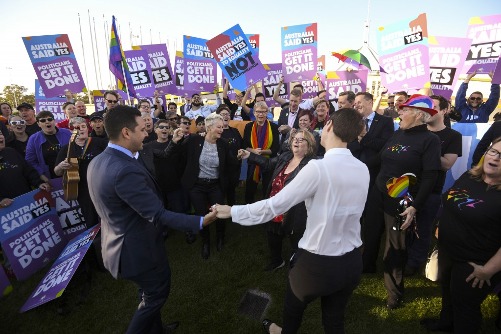 Same-sex marriage campaigners and volunteers cheer as they call on politicians to pass marriage equality legislation during rally outside Parliament H