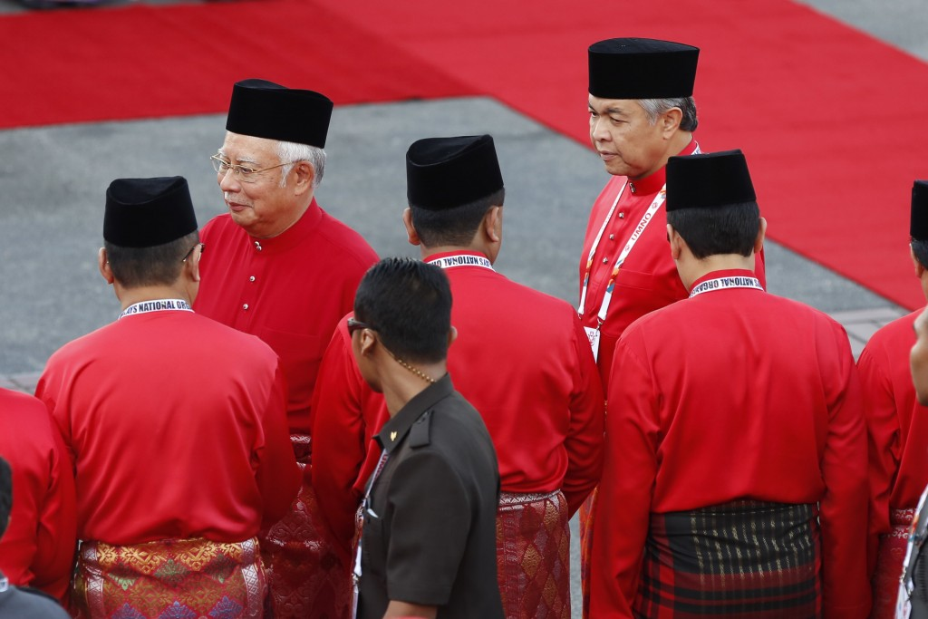 United Malays National Organisation (UMNO) party President and Malaysian Prime Minister Najib Razak, center left, greets members as he arrives for ope