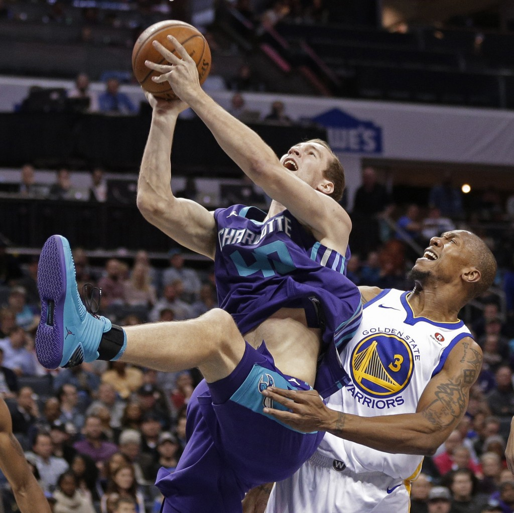 Charlotte Hornets' Cody Zeller (40) is fouled by Golden State Warriors' David West (3) during the first half of an NBA basketball game in Charlotte, N