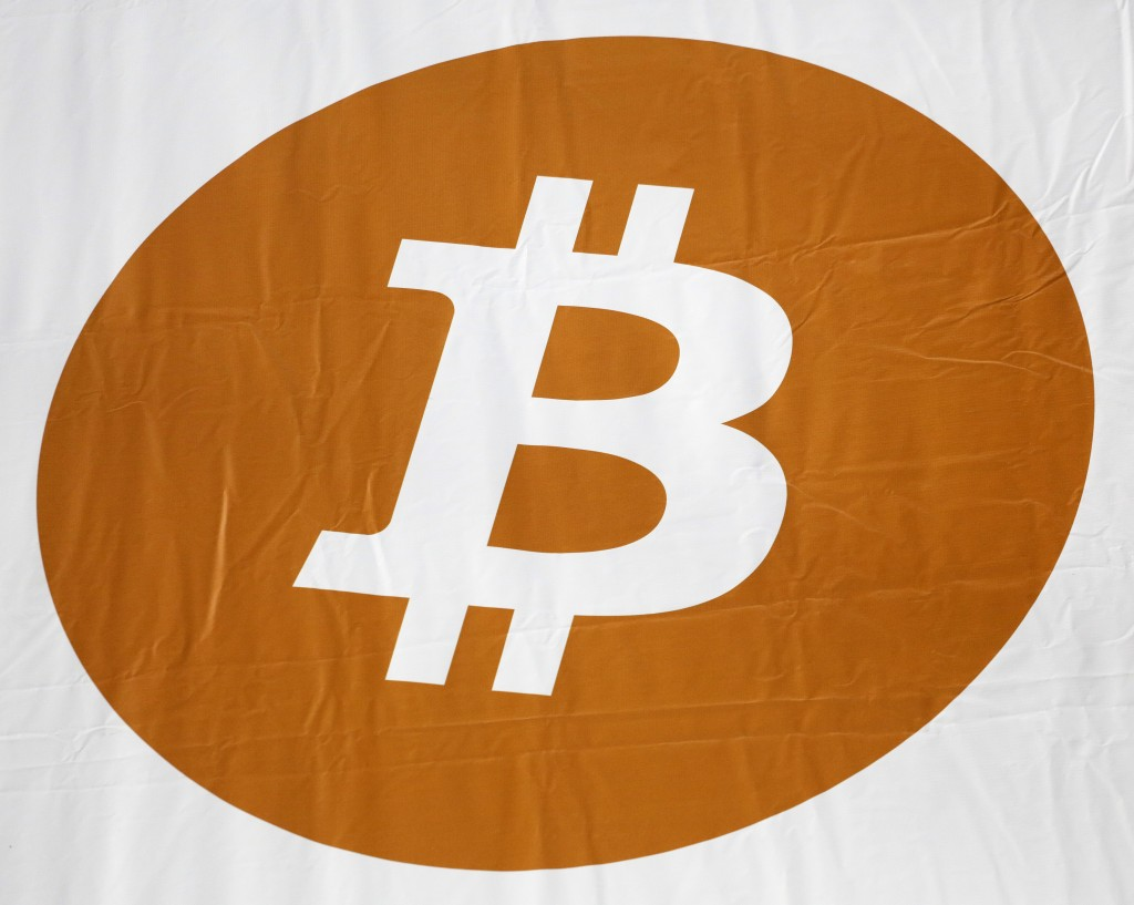 FILE - In this Monday, April 7, 2014, file photo, a bitcoin logo is displayed at the Inside Bitcoins conference and trade show in New York. The bitcoi