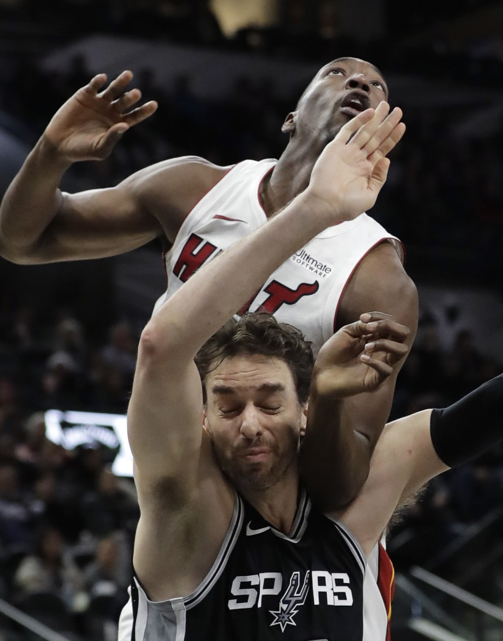 Miami Heat center Bam Adebayo, top, and San Antonio Spurs center Pau Gasol, bottom, jockey for position for a rebound during the first half of an NBA