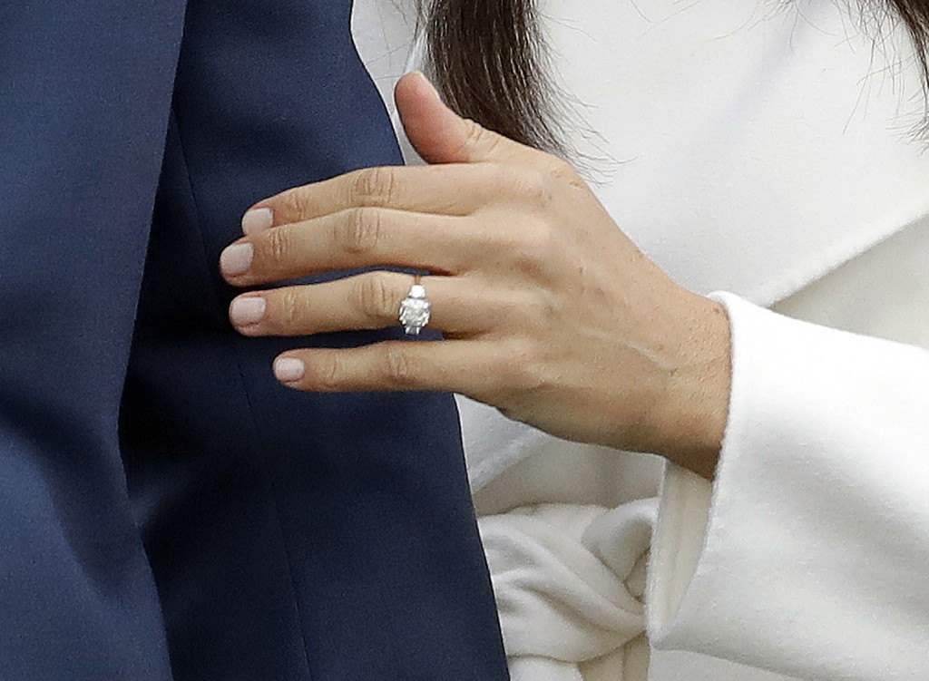 FILE - In this Monday, Nov. 27, 2017 file photo, Britain's Prince Harry's fiancee Meghan Markle shows off her engagement ring as she poses for photogr