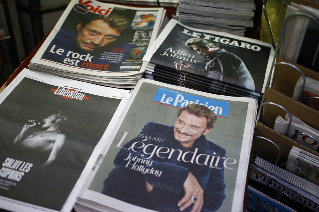 French newspapers with portraits of late rock star Johnny Hallyday are displayed in a street news stand of Paris, France, Thursday, Dec. 7, 2017. John
