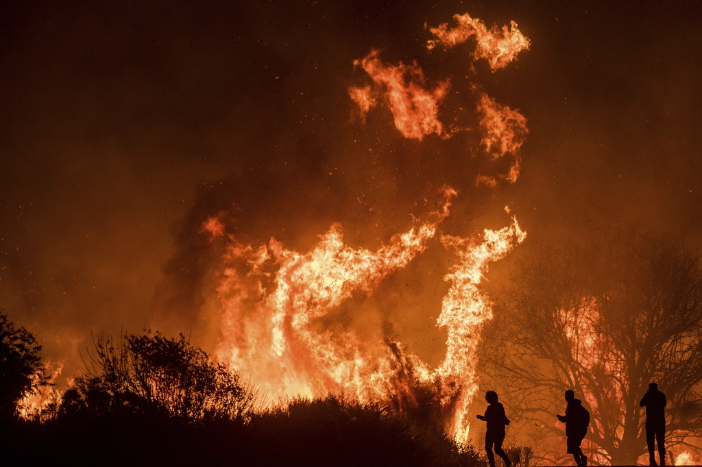 Motorists on Highway 101 watch flames from the Thomas fire leap above the roadway north of Ventura, Calif., on Wednesday, Dec. 6, 2017.  As many as fi