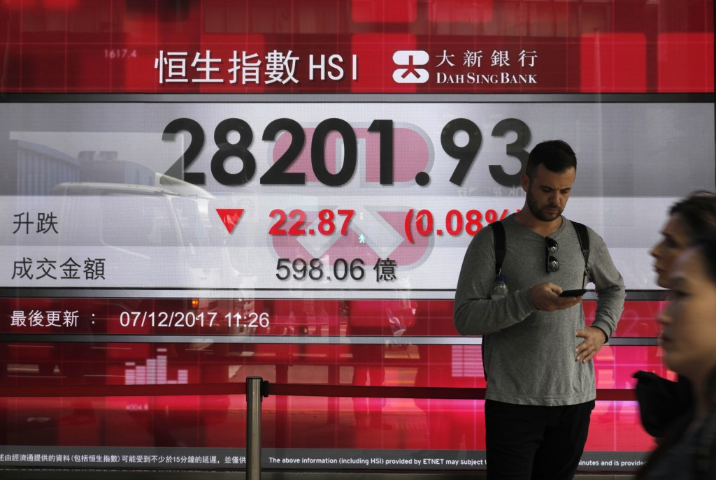 A man stands in front of a bank electronic board showing the Hong Kong share index outside a Hong Kong local bank Thursday, Dec. 7, 2017. Share prices