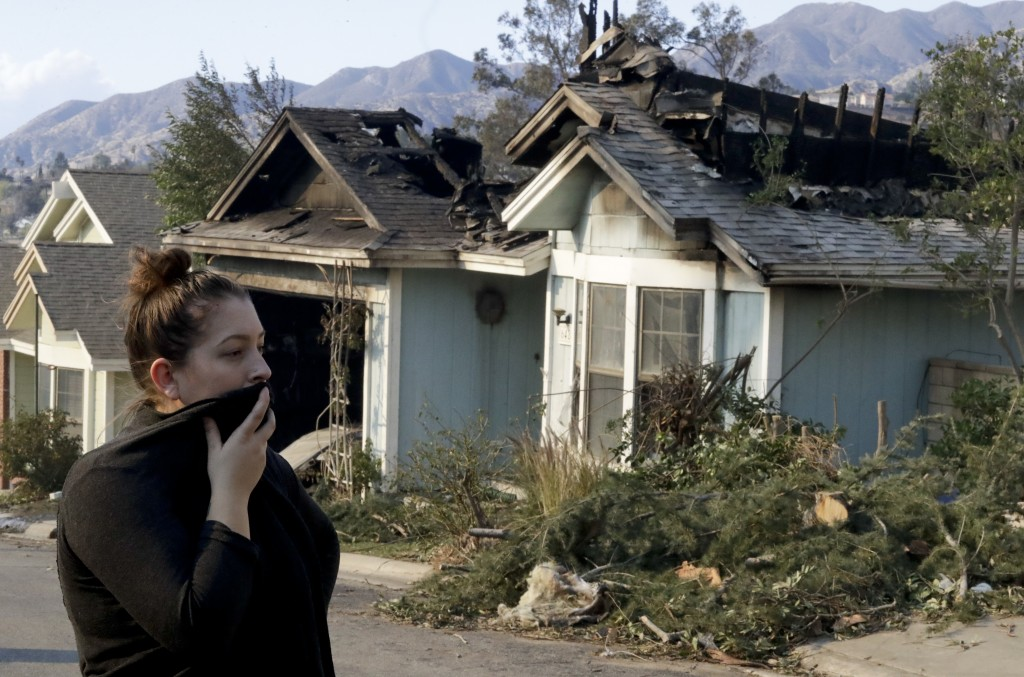 Crystal Shore look over the wildfire damaged neighbors home along Via San Anselmo in the Sylmar area of Los Angeles Wednesday, Dec. 6, 2017. (AP Photo
