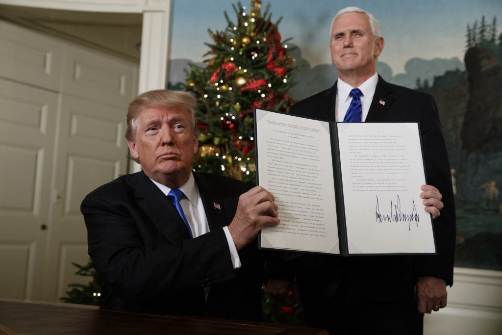 Vice President Mike Pence watches as President Donald Trump holds up a proclamation to officially recognize Jerusalem as the capital of Israel, in the