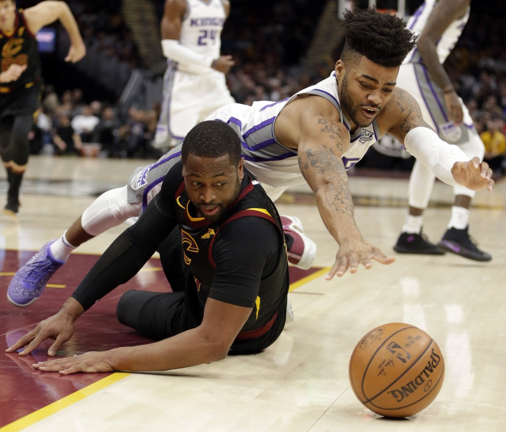 Sacramento Kings' Frank Mason III, right, and Cleveland Cavaliers' Dwyane Wade battle for a loose ball in the first half of an NBA basketball game, We