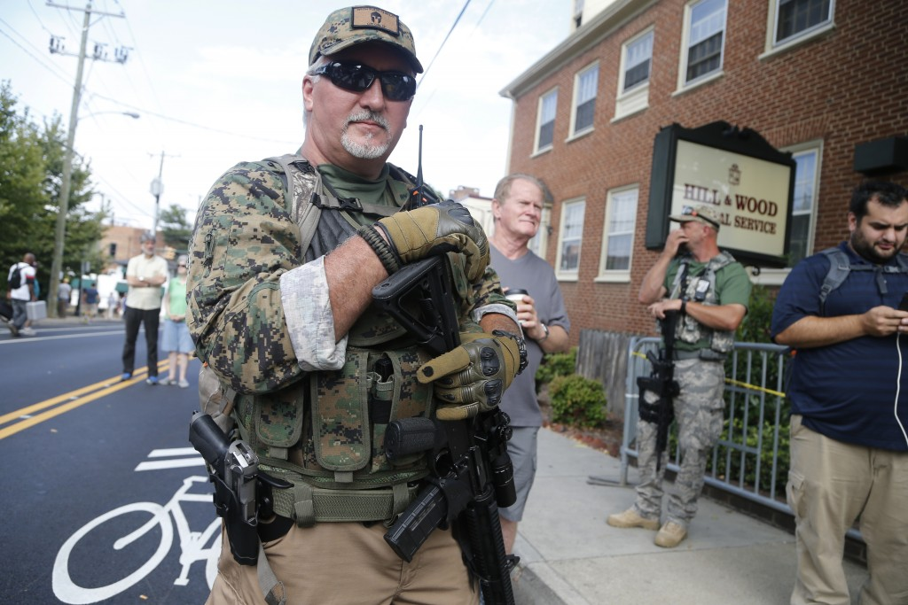 FILE - In this Aug. 12, 2017, file photo, an armed militia member stands guard at a white nationalist rally in Charlottesville, Va. Virginia Democrats