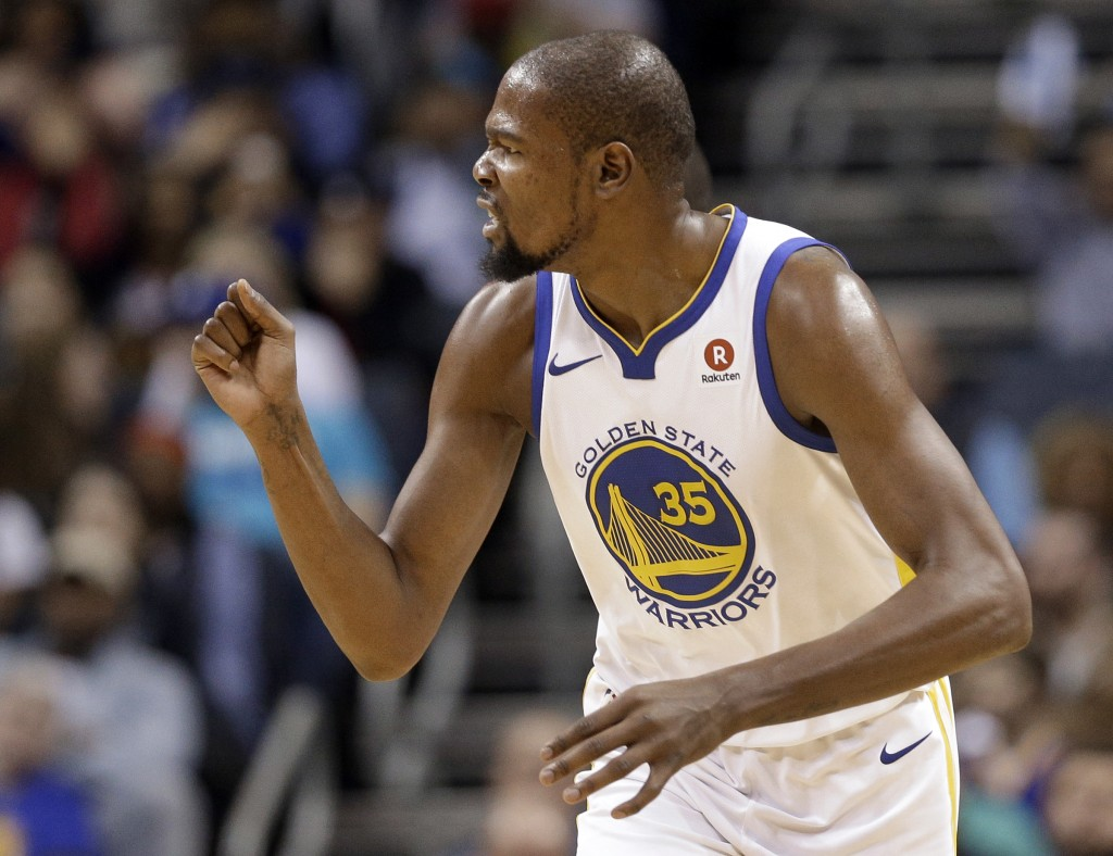 Golden State Warriors' Kevin Durant reacts to making a dunk against the Charlotte Hornets during the first half of an NBA basketball game in Charlotte
