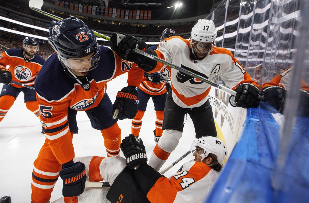 Philadelphia Flyers' Sean Couturier (14) is checked by Edmonton Oilers' Darnell Nurse (25) as Wayne Simmonds (17) checks Darnell Nurse (25) during the