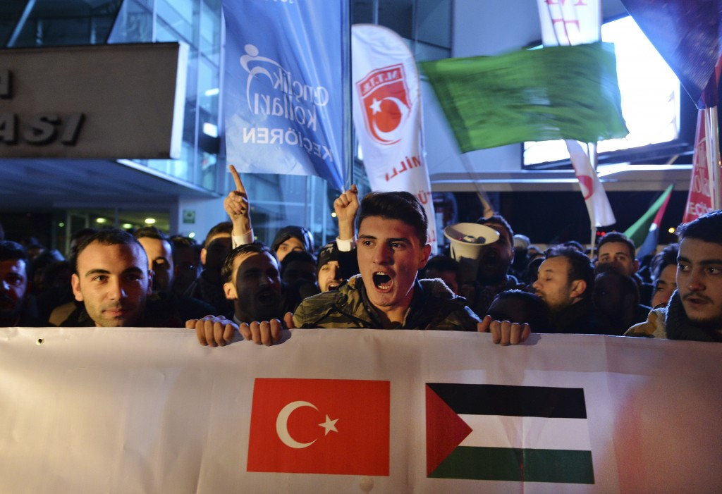 Holding a banner with a Turkish, led and a Palestinian flag, right, protesters chant anti-U.S. slogans during a demonstration near the U.S. embassy in