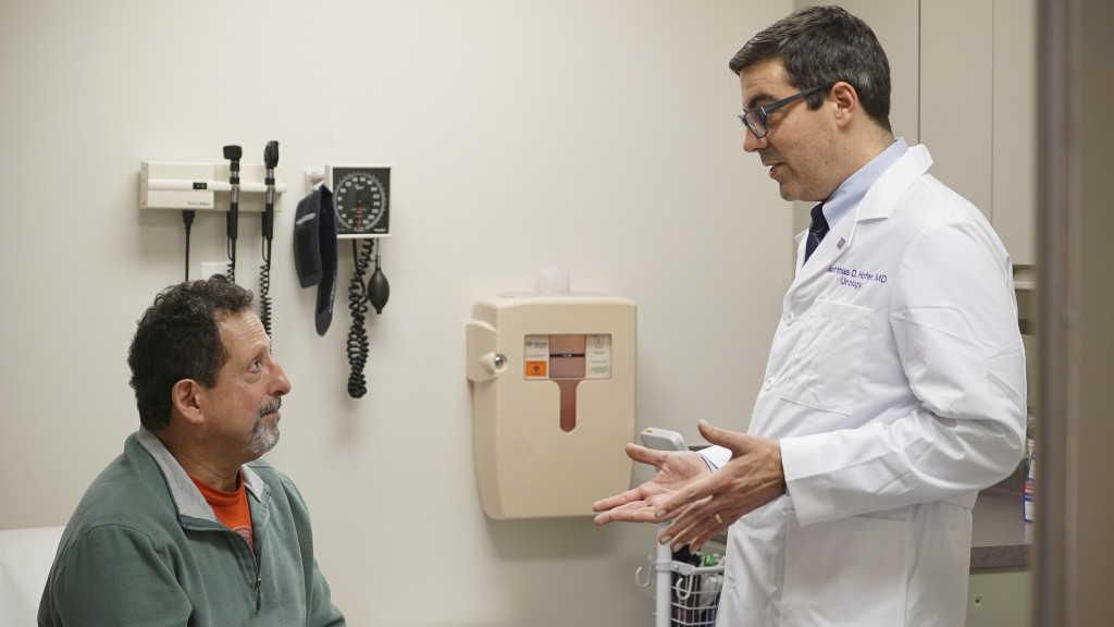 In this Dec. 1, 2017 photo, patient Daniel Lobello, left, speaks with Dr. Matthias Hofer, a urologist at Northwestern Memorial Hospital in Chicago. Lo