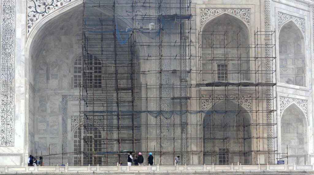 In this Tuesday, Dec. 5, 2017, file photo, tourists walk past the discolored wall of the Taj Mahal caused by environmental pollution which stands out
