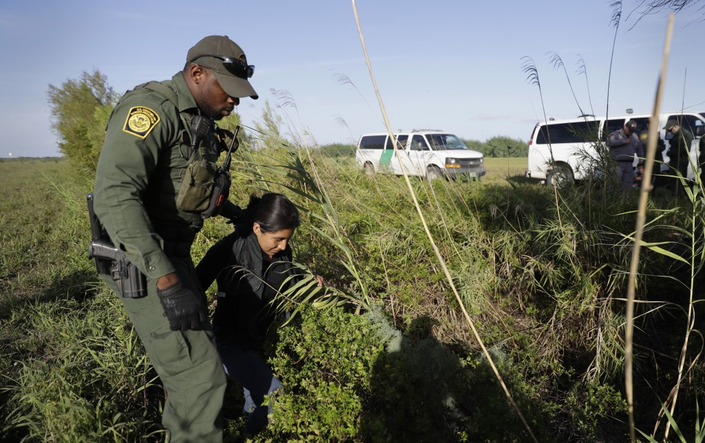 In this Aug. 11, 2017, photo a U.S. Customs and Border Patrol agent escorts an immigrant suspected of crossing into the United States illegally along