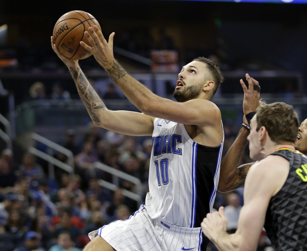 Orlando Magic's Evan Fournier (10) goes past Atlanta Hawks' Tyler Cavanaugh, right, for a shot during the first half of an NBA basketball game, Wednes