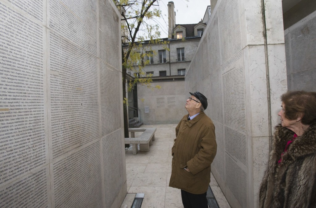 In this photo taken on Tuesday, Dec. 5, 2017, French Nazi hunter Serge Klarsfeld looks at the name of his father who died in Auschwitz engraved on the